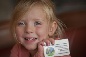 young child holding library card