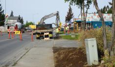 Public Works Department personnel remove sod built up over time at the sidewalk in front of Cosmic Kitchen.